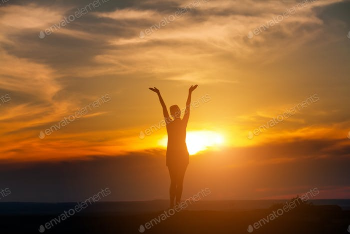 The woman with yoga posture on the mountain at sunset.