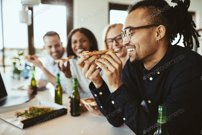 Laughing African American businessman having beers and pizza with coworkers