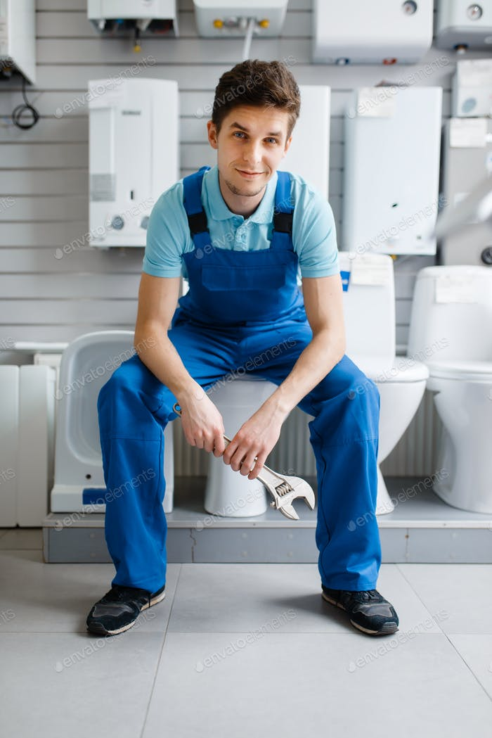 Plumber in uniform sitting on toilet in plumbering