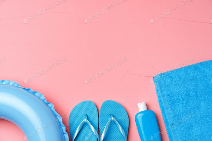Beach concept with blue rubber ring, towel, flip-flops and moistrizer on pink background