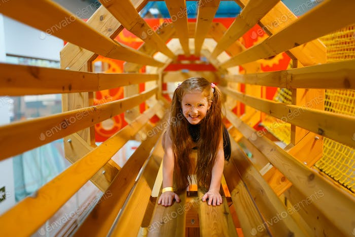 Little girl playing in wooden labyrinth, playroom
