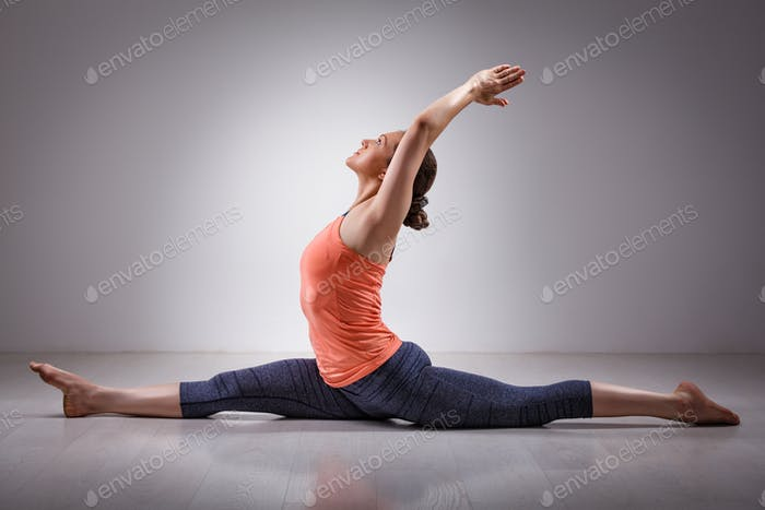 Sporty fit woman doing yoga asana Hanumanasana