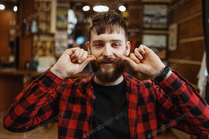 Barber twists his mustache, retro style barbershop