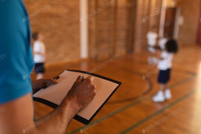 Close-up of basketball coach writing on clipboard at basketball court in school