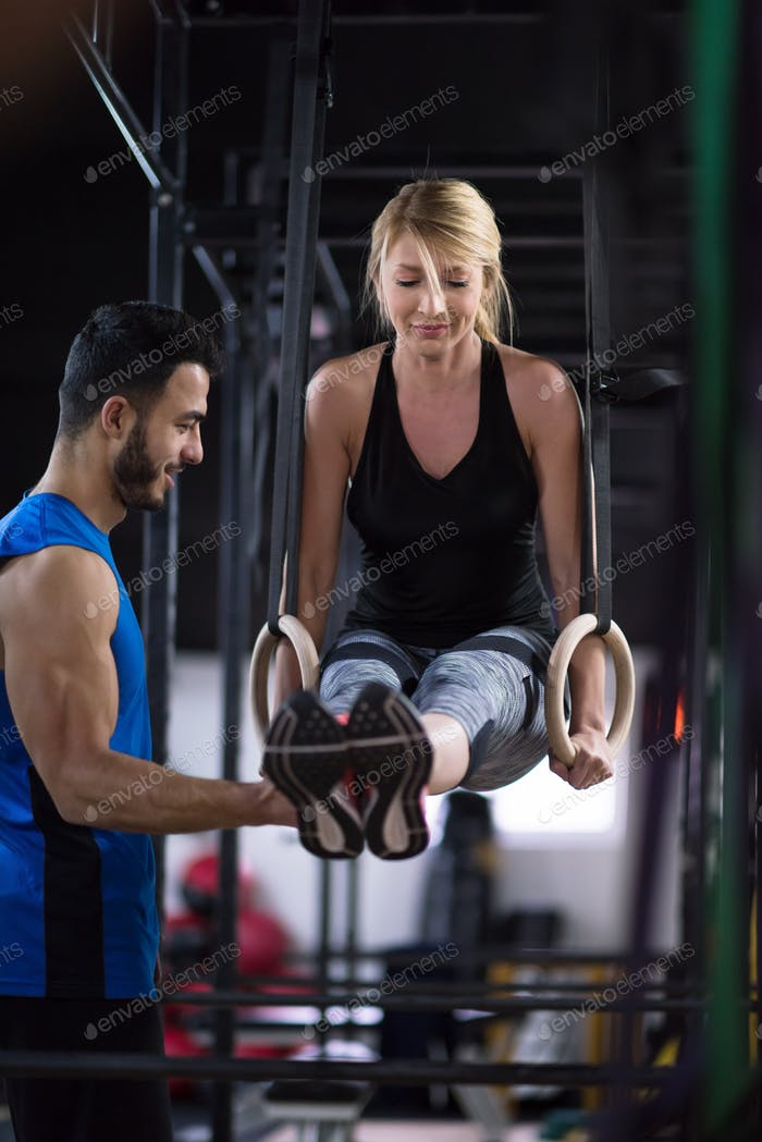 woman working out with personal trainer on gymnastic rings
