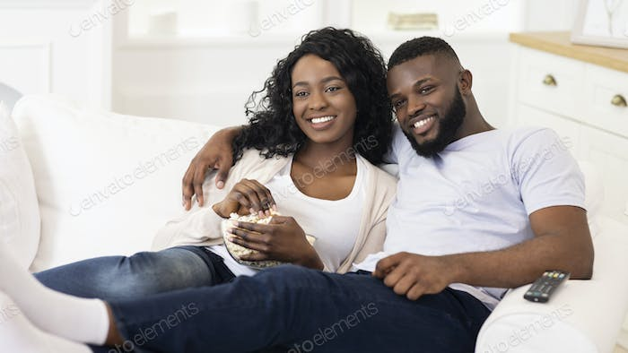 Afro couple watching tv, sitting with popcorn at home