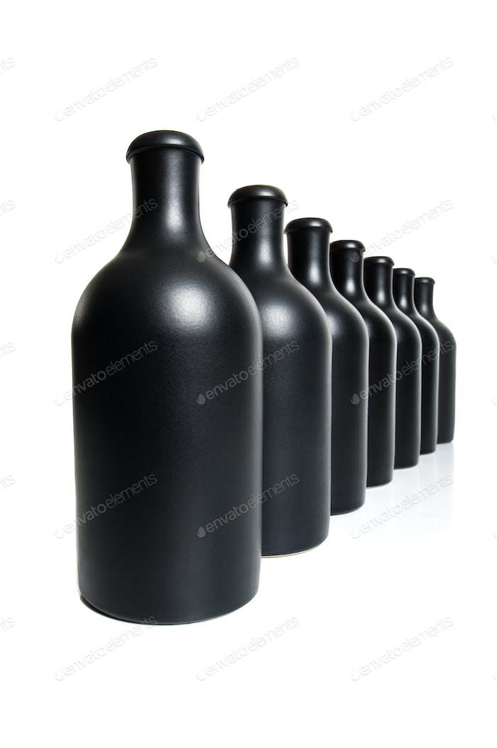 Seven matte black bottles on a white background.