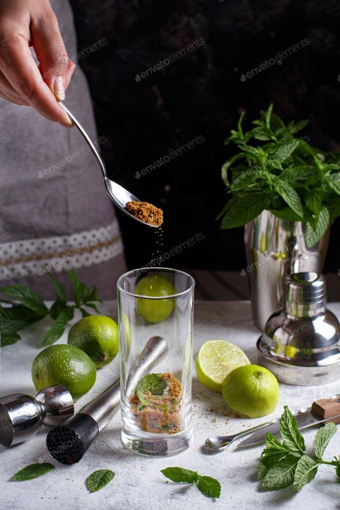 Sifting sugar in a homemade refreshing mojito cocktail