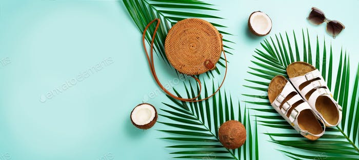 Round rattan bag, coconut, birkenstocks, palm branches, sunglasses on blue background. Banner. Top