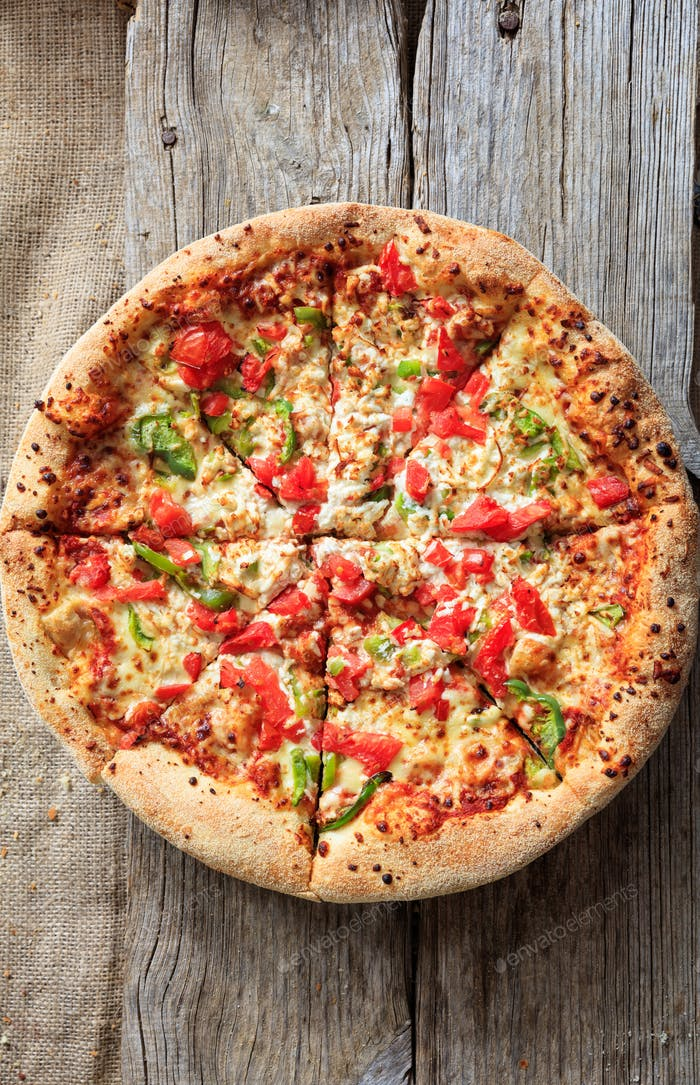 Fast food concept. Pizza with crunchy dough and fresh vegetables on wooden surface.