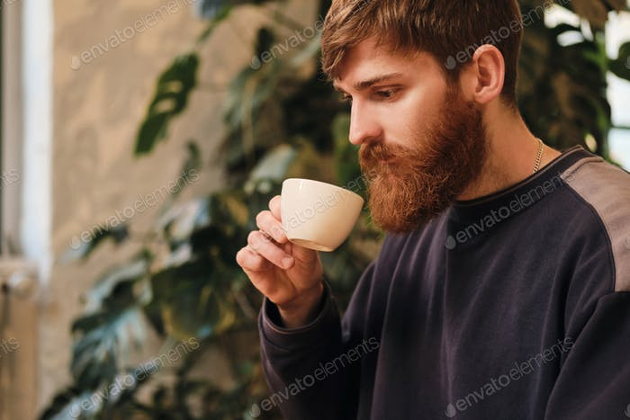 Young attractive bearded man drinking coffee resting in cafe