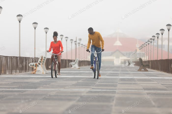 Couple riding bicycle at promenade on a sunny day. Male standing on the bicycle