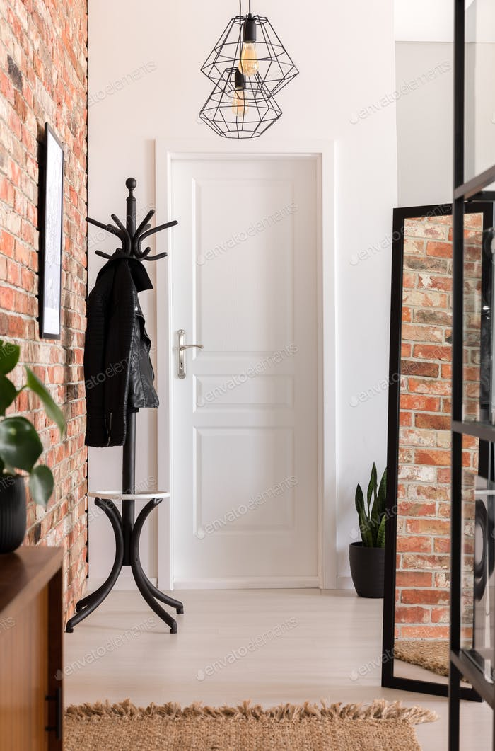 White and brick walled entrance hall interior in real photo with