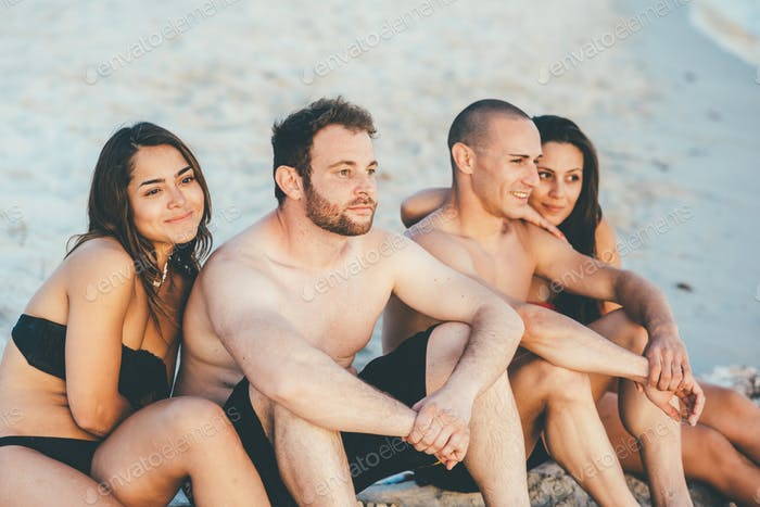 Group of young beautiful multiethnic woman and man friends sunbathing