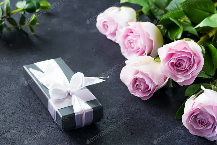 Pink roses and a gift box on a stone background. Vintage style, retro interior with flowers. Space
