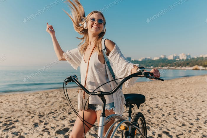 young attractive blond smiling woman walking on beach with bicycle