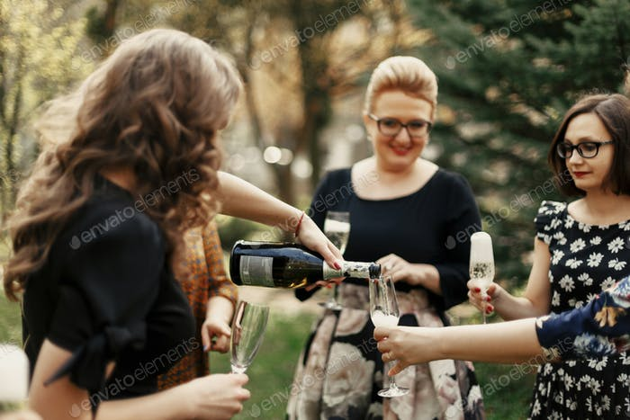 group of luxury elegant women celebrating with champagne