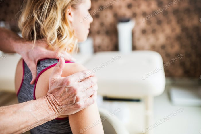 Unrecognizable physiotherapist working with a female patient.