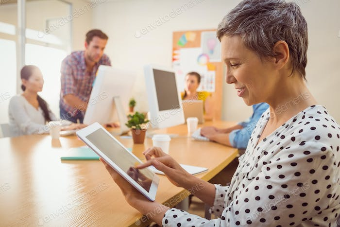 Smiling creative businesswoman using a tablet in the office