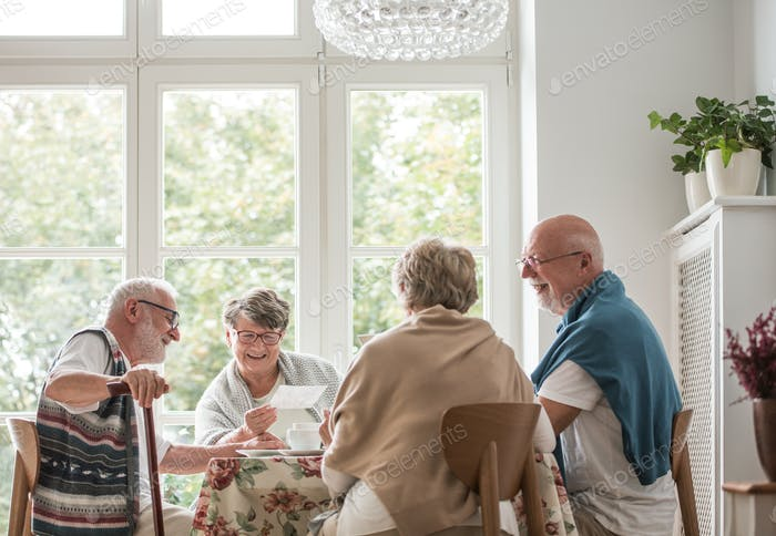 Group of senior friends sitting together at the table at nursing home dining room