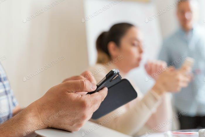 Mann mit Handy während der Geschäftstreffen