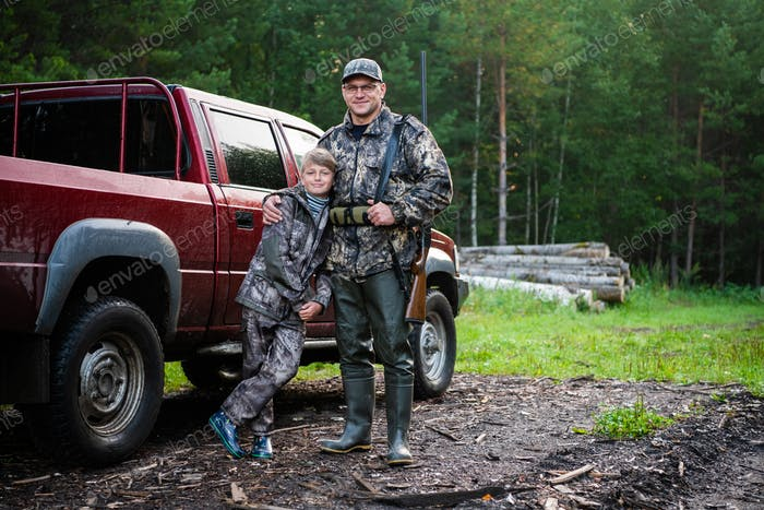 Father and son came to the forest for hunting together. Standing with a shotgun rifle in front of