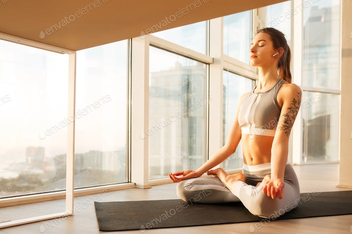 Young lady in sporty top and leggings sitting in lotus pose meditating on yoga mat over window