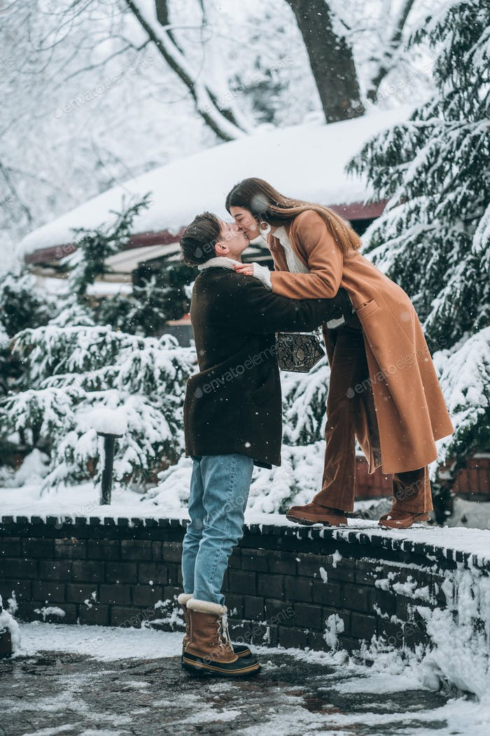young guy and beautiful girl kiss in a snowy park