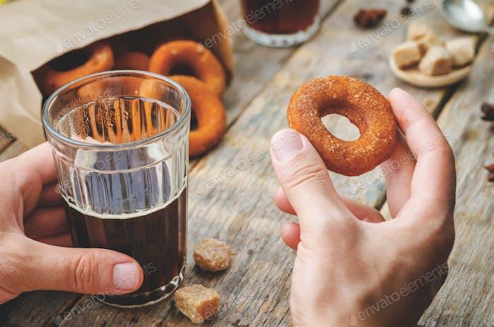 Mann hält Glas Kaffee und Kürbis Donut