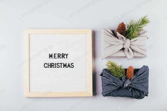 Christmas eco-friendly gift box furoshiki. Lightbox with text Merry Christmas. Zero waste concept