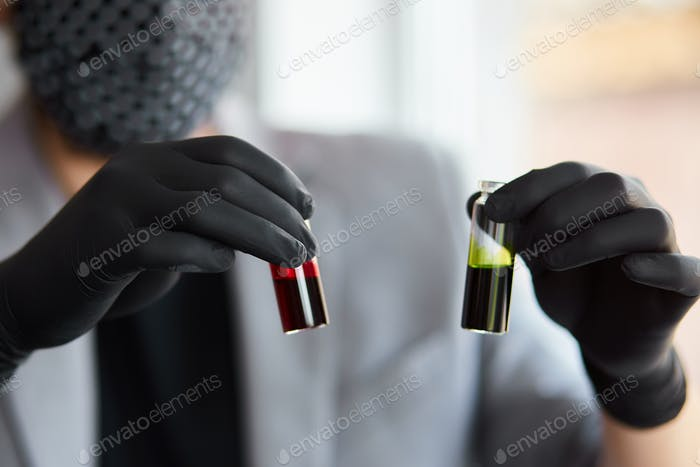 Young man holding test tubes with blood and antidote in his hand.