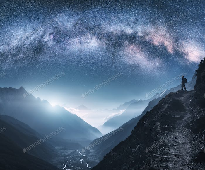 Arched Milky Way, woman and mountains at night