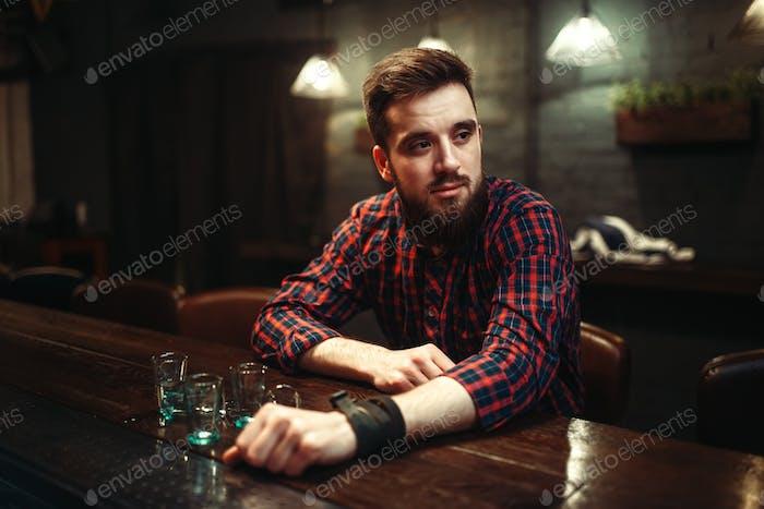 Sad man sitting at bar counter, alcohol addiction