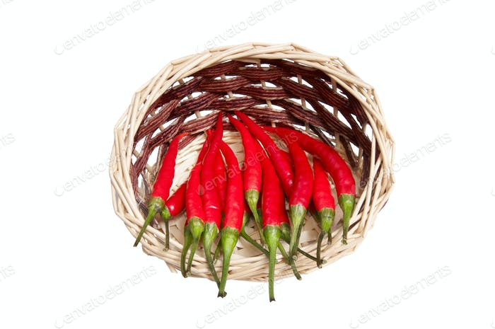 Wooden basket full of red peppers.