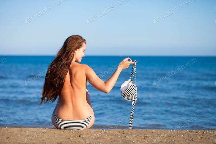 Woman on the beach in topless holding bikini