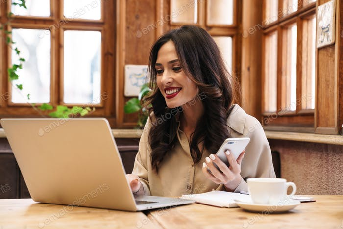 Image of happy adult woman using cellphone and working with laptop
