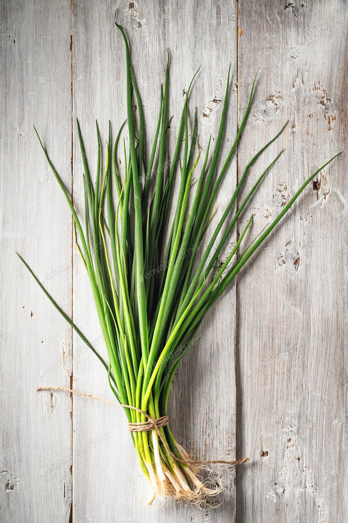Green onion on the white wooden table vertical