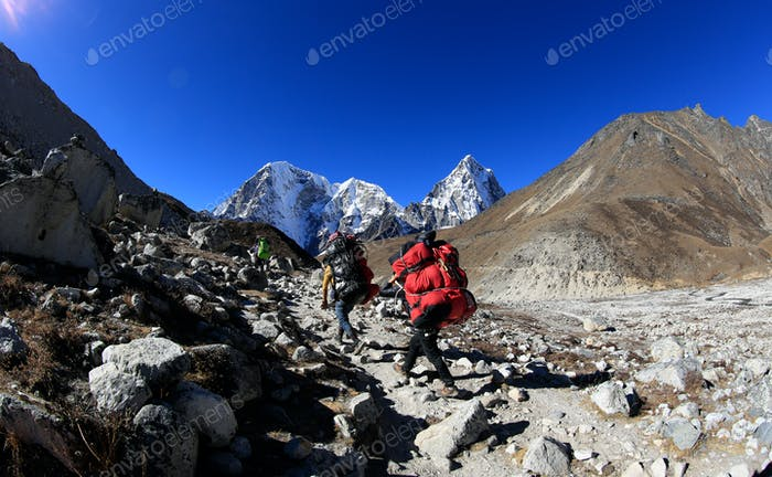 Porters carrying heavy packages climbing the ebc(everest base camp) mountains