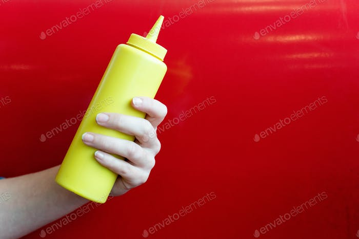 Hand holding a mustard bottle on a red background in a diner