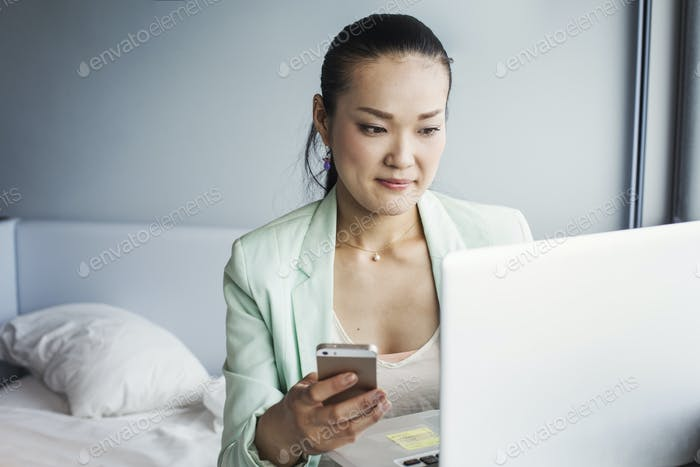 A business woman preparing for work, sitting on a bed using a laptop and holding her smart phone.