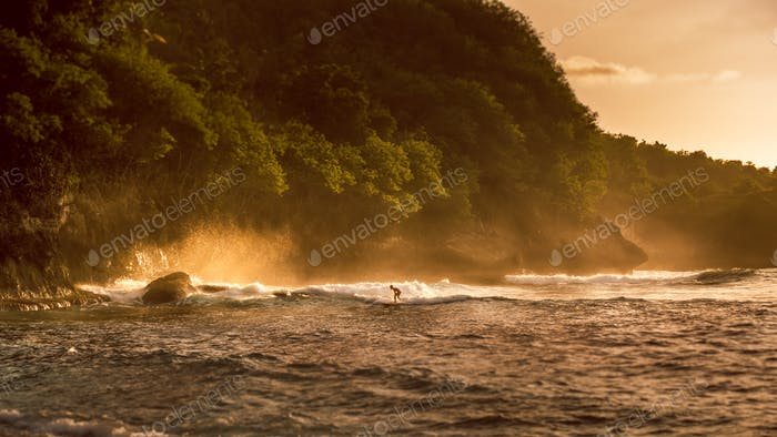 Local Kids surf on Waves in Sunset light, Beautiful Crystal Bay, Nusa Penida Bali