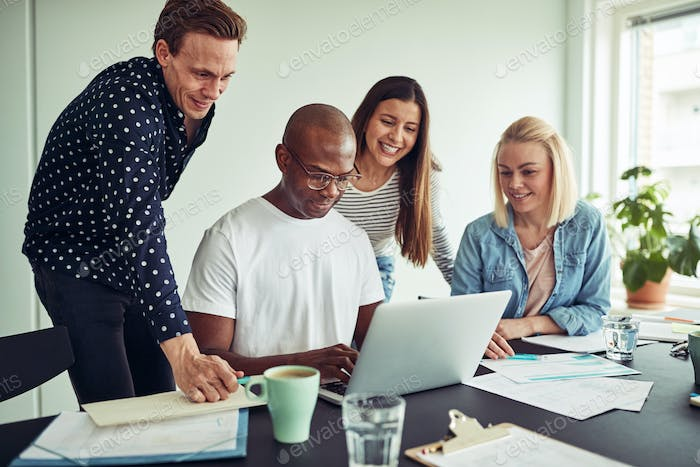 Smiling group of businesspeople working online together in an office