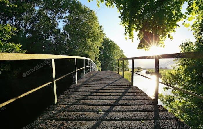 wooden bridge via river on sunny day