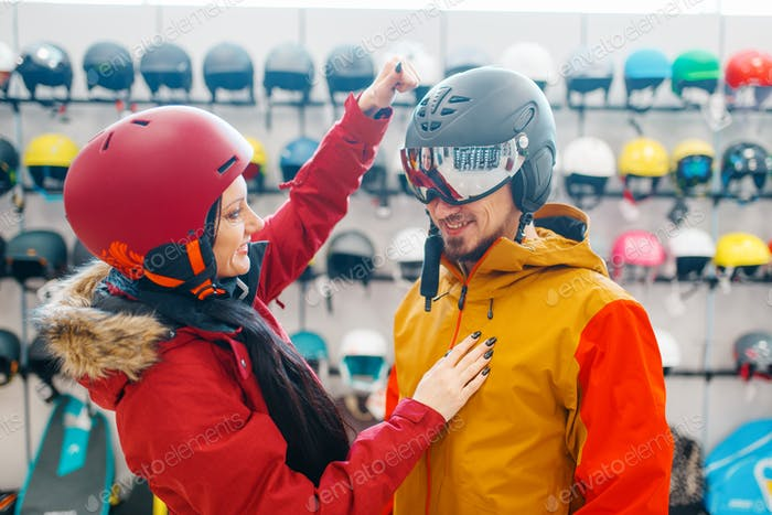Couple check the strength of the ski helmet