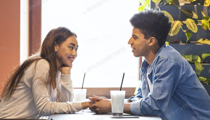 Young couple in love holding hands, having conversation