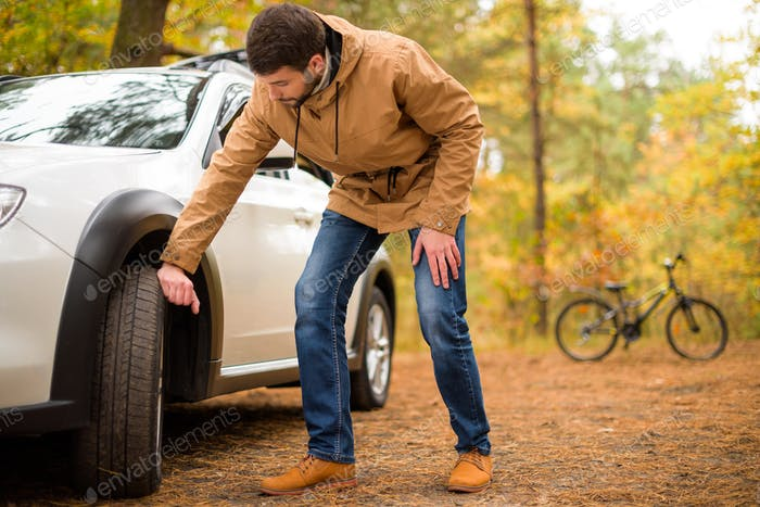 Young bearded man checking car tyre in autumn forest