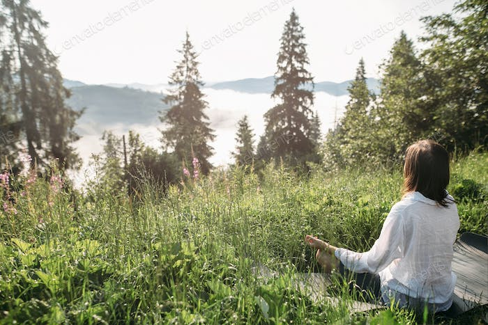 Young woman practicing yoga and sitting in lotus position on top of mountain