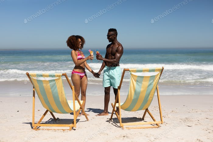 Mixed race couple drinking cocktails on the beach
