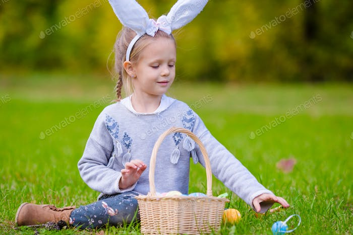 Portrait of kid on Easter playing with eggs outdoor