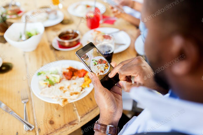 hands with smartphone picturing food at restaurant